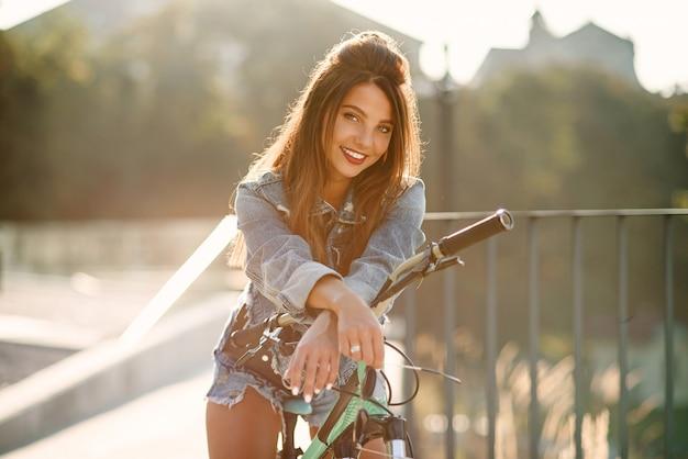 Atrakcyjna kusząca młoda dziewczyna w modnych dżinsach nosi stylowe okulary, siedzi na rowerze i pozuje przed kamerą w letni wieczór. zwolnione tempo