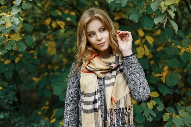 Atrakcyjna ładna młoda kobieta o niebieskich oczach w szaliku vitage w eleganckim płaszczu w parku na tle jesiennych żółto-zielonych liści