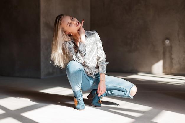 Atrakcyjna ładna młoda seksowna kobieta w modnej koszuli w niebieskie dżinsy zgrywanie w zielonych kowbojskich butach siedzi w słoneczny wiosenny dzień w pomieszczeniu