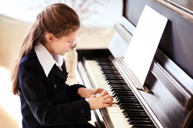 Atrakcyjna mała dziewczynka gra na pianinie