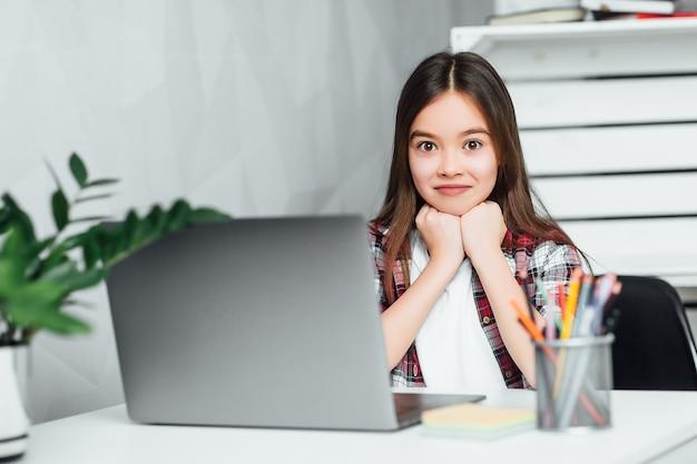 Atrakcyjna mała dziewczynka korzysta z laptopa w domu w wolnym czasie