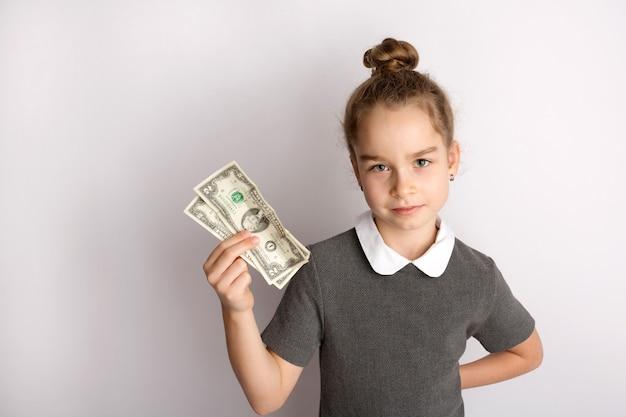 Atrakcyjna mała dziewczynka w surowej szkolnej sukience, stoi na białym tle, gestykuluje rękami, podziwia radosny wyraz twarzy. zdjęcie wysokiej jakości