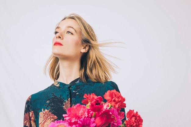 Atrakcyjna marzycielska kobieta z bukietem kwiaty