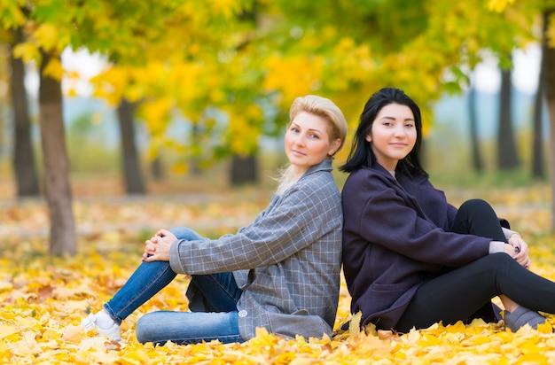 Atrakcyjna matka i córka relaks w parku, siedząc razem tyłem do siebie na kolorowych żółtych liści jesienią