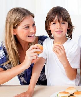 Atrakcyjna matka i jej syn jedzenia hamburgery