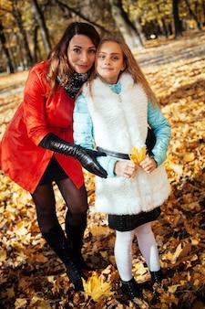 Atrakcyjna matka i jej szczęśliwa córeczka razem spaceru w parku jesienią