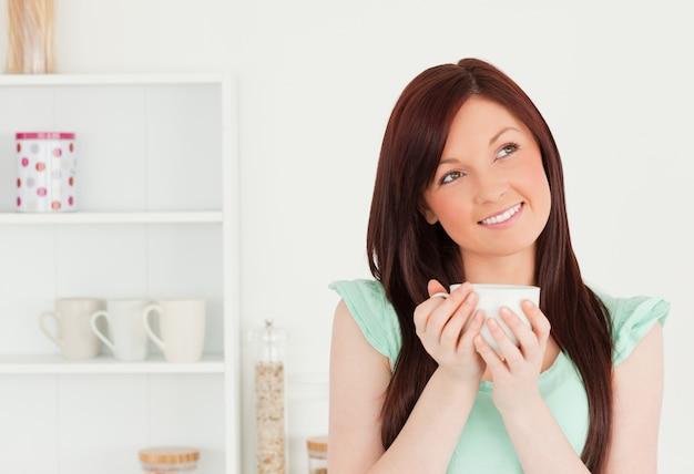Atrakcyjna miedzianowłosa kobieta cieszy się jej śniadanie w kuchni