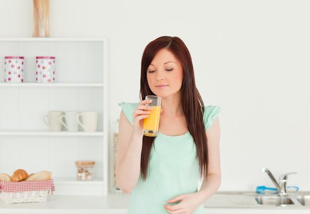 Atrakcyjna miedzianowłosa kobieta cieszy się szkło sok pomarańczowy w kuchni