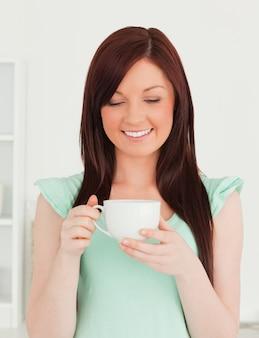 Atrakcyjna miedzianowłosa kobieta ma jej śniadanie w kuchni