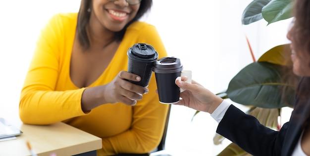 Atrakcyjna młoda afroamerykańska bizneswoman nosząca ochronną maskę na twarz zapobiega piciu czarnej kawy przez wirusa covid-19