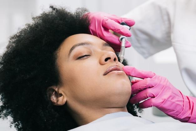 Atrakcyjna młoda afrykanka dostaje odmładzające zastrzyki na twarz. siedzi spokojnie w klinice. ekspert kosmetyczki wypełnia kobiece zmarszczki kwasem hialuronowym.
