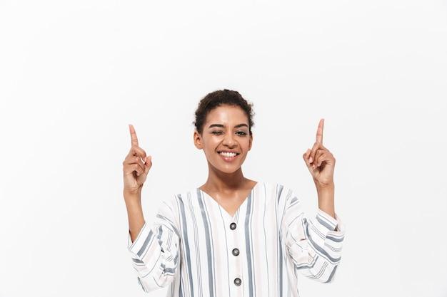 Atrakcyjna młoda afrykańska kobieta nosząca zwykłe ubrania, stojąca na białym tle nad białą ścianą, wskazująca w górę