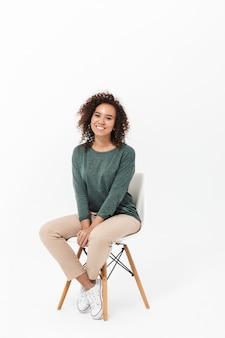 Atrakcyjna młoda afrykańska kobieta siedzi na krześle na białym tle nad białą ścianą, pozuje