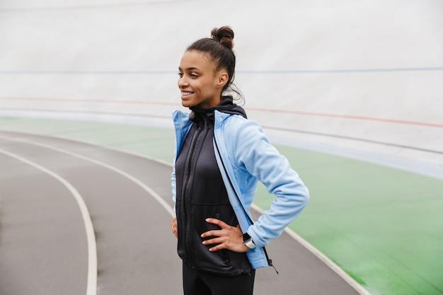 Atrakcyjna młoda afrykańska sportsmenka odpoczywa po biegu na stadionie
