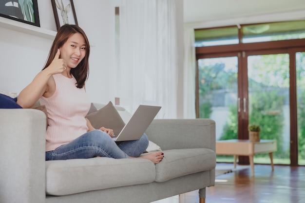 Atrakcyjna młoda azjatycka bizneswoman pokazująca kciuk w górę w celu świętowania osiągnięcia lub sukcesu podczas korzystania z laptopa w domu