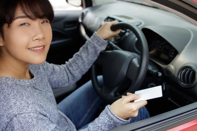 Atrakcyjna młoda azjatykcia kobieta dumnie pokazuje jej prawo jazdy.