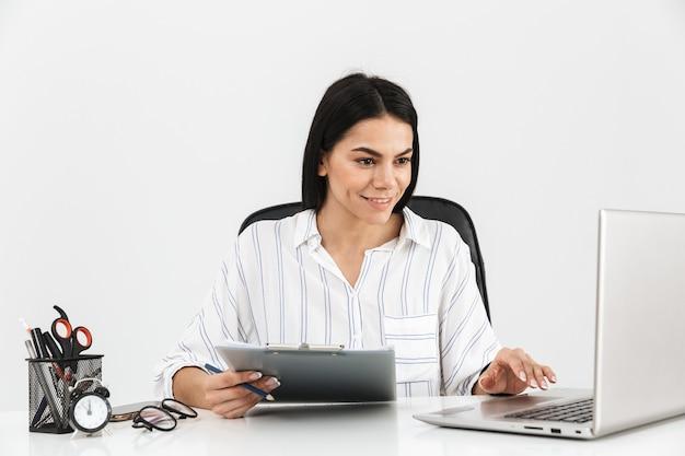 Atrakcyjna młoda bizneswoman siedzi przy biurku na białym tle nad białą ścianą, pracując z komputerem i dokumentami