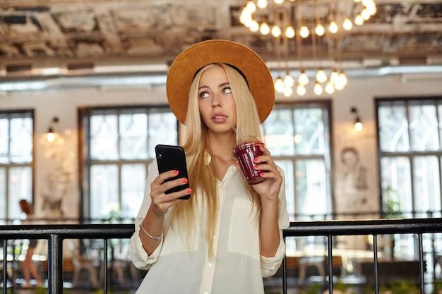 Atrakcyjna młoda blondynka pije smoothie ze słomką, czekając na swoje zamówienie w kawiarni, trzymając smartfon w dłoni i patrząc na bok z zainteresowaniem