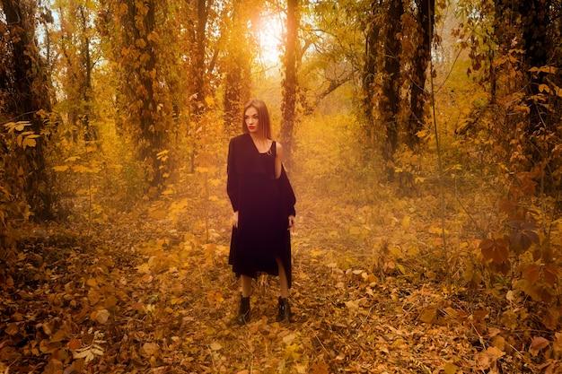 Atrakcyjna młoda blondynka w czarnym płaszczu, odwracając się w złotym lesie jesienią