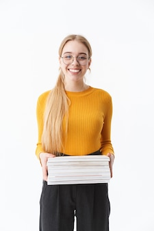 Atrakcyjna Młoda Blondynka W Swetrze Stojącym Na Białym Tle Nad Białą ścianą, Trzymająca Stertę Książek Premium Zdjęcia