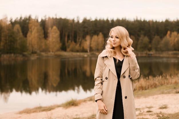 Atrakcyjna młoda blondynka z kręconymi włosami i makijażem w beżowy trencz na tle złotej jesieni jeziora