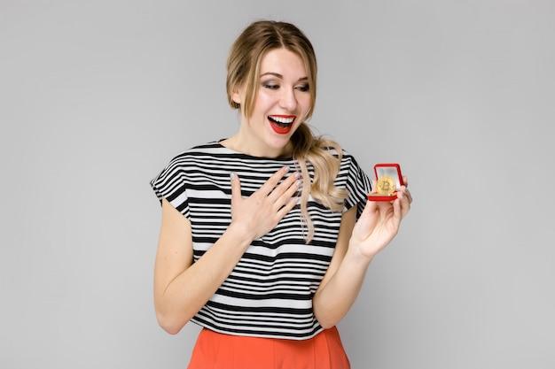 Atrakcyjna młoda blondynki dziewczyna ono uśmiecha się w pasiastej bluzce pokazywać bitcoin jako kryptowaluty pojęcia pozycja na szarym tle