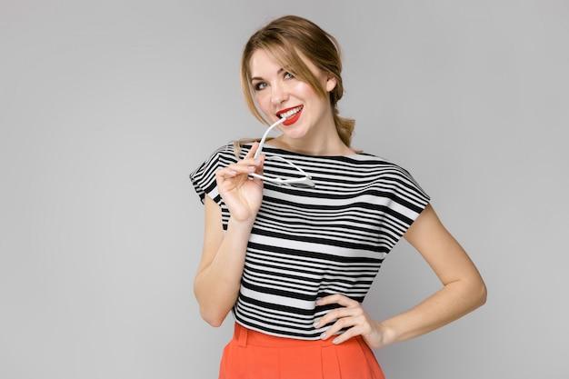 Atrakcyjna młoda blondynki dziewczyna ono uśmiecha się w pasiastej bluzce trzyma jej szkła stoi na szarym tle