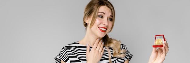 Atrakcyjna młoda blondynki dziewczyna w pasiastej bluzce ono uśmiecha się pokazywać bitcoin