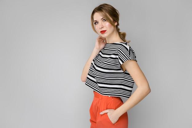 Atrakcyjna młoda blondynki dziewczyna w pasiastej bluzki poważnym ufnym mieniu jej włosiana pozycja na szarym tle