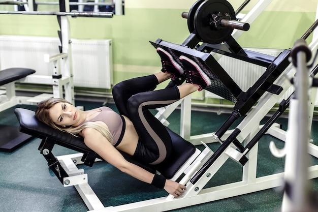 Atrakcyjna młoda blondynki kobieta robi sile trenować na gym.