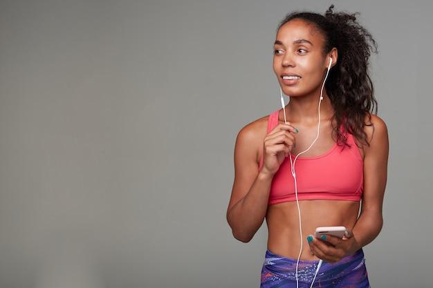 Atrakcyjna młoda brązowooka brunetka sportowa dama o ciemnej skórze słucha muzyki w słuchawkach przed porannym treningiem, stojąc