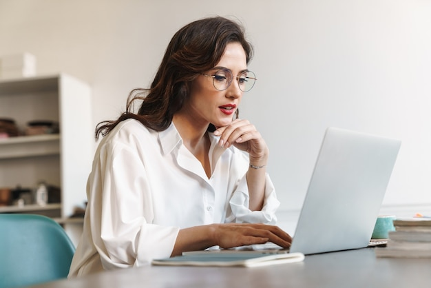 Atrakcyjna młoda brunetka bizneswoman siedzi przy stoliku kawiarnianym z laptopem w pomieszczeniu