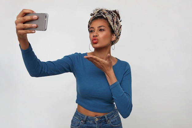 Atrakcyjna młoda brunetka ciemnoskóra kobieta wysyła pocałunek w powietrze podczas robienia sobie zdjęcia na telefon komórkowy, stojąc na białym tle