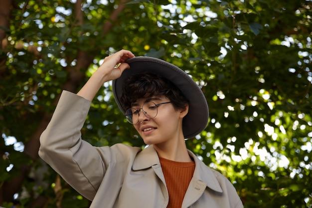 Atrakcyjna młoda brunetka dama z krótką fryzurą patrząc w dół w zamyśleniu i trzymając kapelusz z podniesioną ręką, chodząc po zielonym parku miejskim w modnym ubraniu i okularach