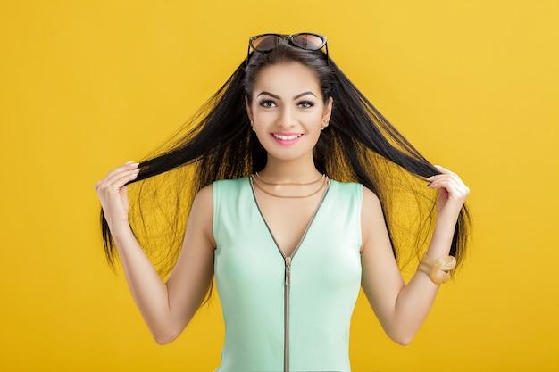 Atrakcyjna młoda brunetka kobieta w zielonym stroju kąpielowym na żółto. uśmiechnięta kobieta w turkusowym body