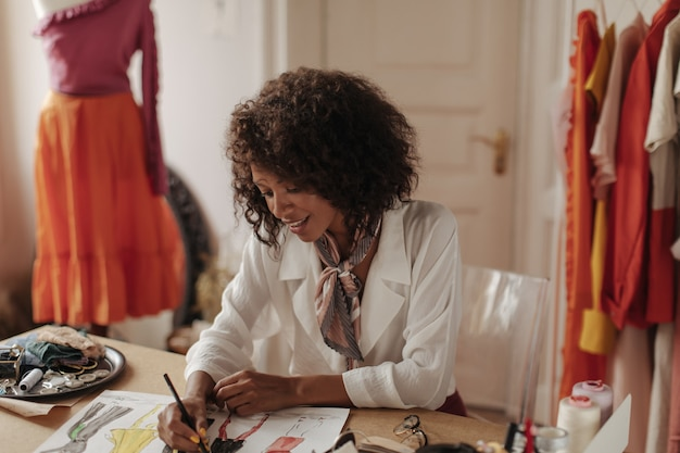 Atrakcyjna młoda brunetka kręcona ciemnoskóra kobieta w białej modnej bluzce projektuje kolekcję mody i siedzi w przytulnym biurze