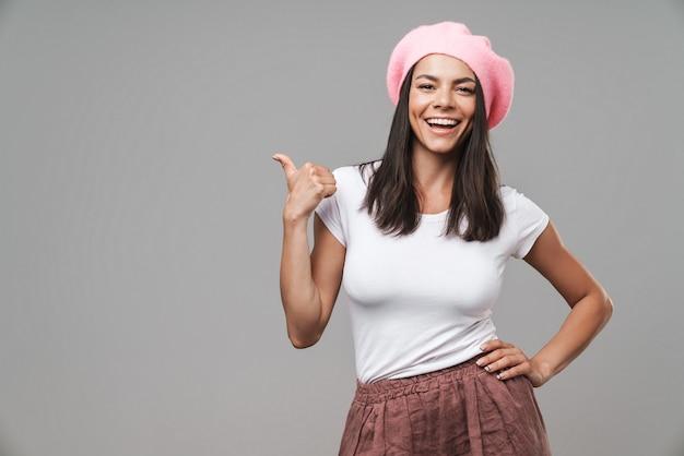 Atrakcyjna młoda brunetka w berecie stojąca na białym tle nad szarą ścianą, prezentująca miejsce na kopię