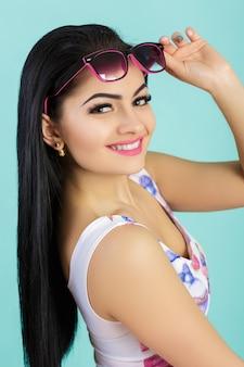 Atrakcyjna młoda brunetka w różowym podkoszulku na niebieskiej uśmiechniętej dziewczynie w okularach przeciwsłonecznych