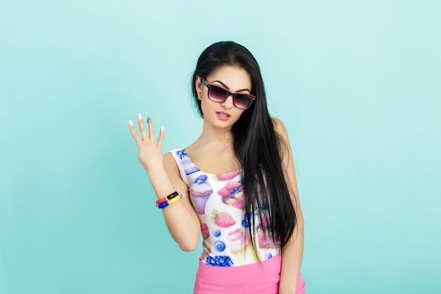 Atrakcyjna młoda brunetka w różowym podkoszulku na niebiesko