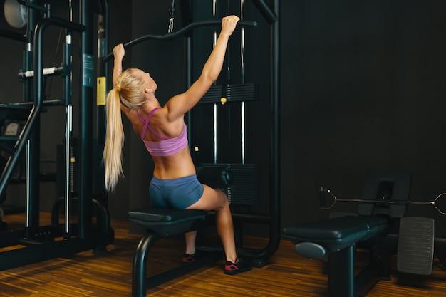 Atrakcyjna młoda caucasian dziewczyna w sporcie jest ubranym pracujące ręki i kręgosłup