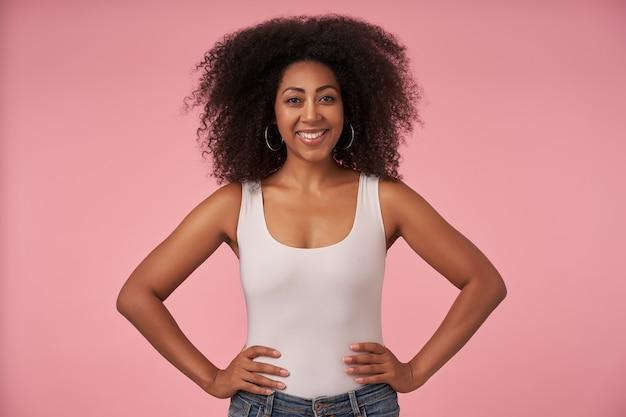 Atrakcyjna młoda ciemnoskóra dama z przypadkową fryzurą, ubrana w białą koszulę i dżinsy, pozująca na różowo z szerokim, czarującym uśmiechem i trzymająca ręce na jej talii