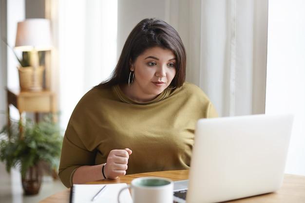 Atrakcyjna młoda ciemnowłosa kobieta z krągłym ciałem przy użyciu zwykłego laptopa do pracy zdalnej, pije kawę i patrzy na ekran z skoncentrowanym wyrazem twarzy. technologia i styl życia