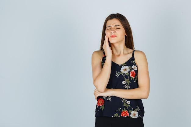 Atrakcyjna młoda dama cierpi na okropny ból zęba w bluzce i wygląda na zirytowaną, widok z przodu.