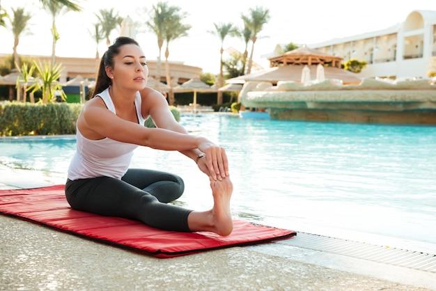 Atrakcyjna młoda dama fitness wykonuje ćwiczenia rozciągające