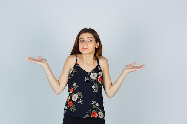 Atrakcyjna młoda dama pokazując bezradny gest w bluzce i patrząc zdezorientowany. przedni widok.