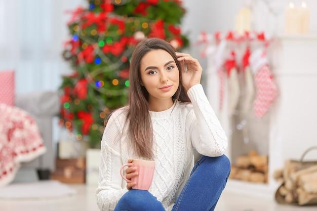 Atrakcyjna młoda dama siedzi w domu z filiżanką herbaty
