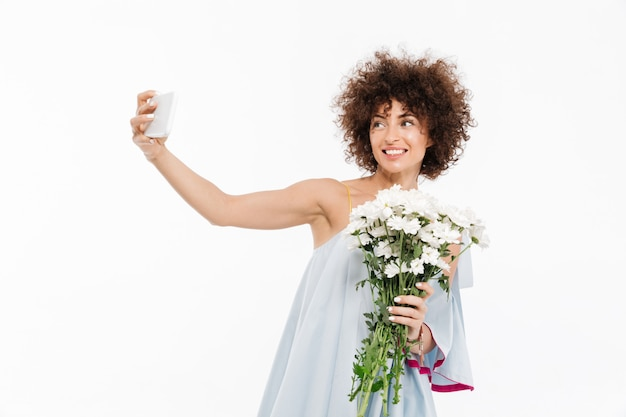 Atrakcyjna młoda dama trzyma bukiet kwiatów