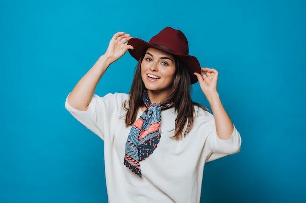 Atrakcyjna młoda dama trzyma zakochaną czapkę, ubrana w biały sweter, burgundowa czapka z rondem i kolorową apaszkę na szyi, uśmiecha się nieśmiało. izolowanych na niebieskim tle