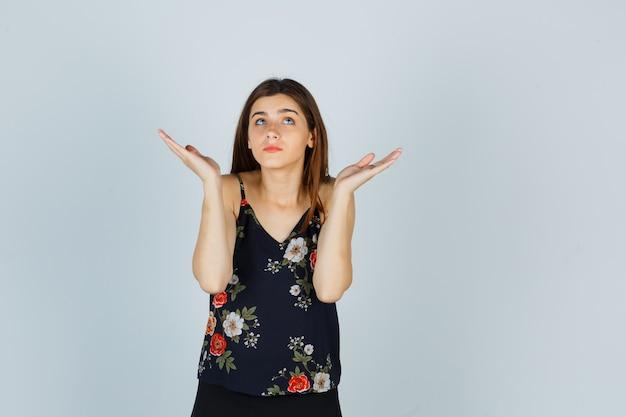 Atrakcyjna młoda dama w bluzce pokazujący bezradny gest i patrząc zdezorientowany, widok z przodu.