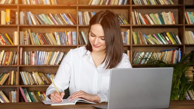 Atrakcyjna młoda dama w stylowej białej bluzce pisze w papierowym notatniku podczas rozmowy wideo na współczesnym laptopie przy stole przy stojakach z książkami